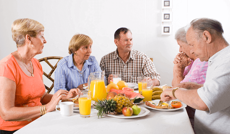 elderly sharing food in the table