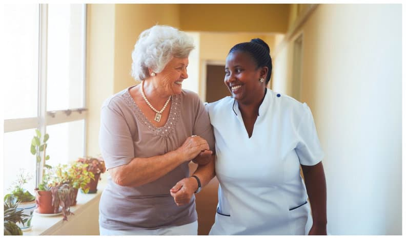 caregiver and senior woman smiling each other